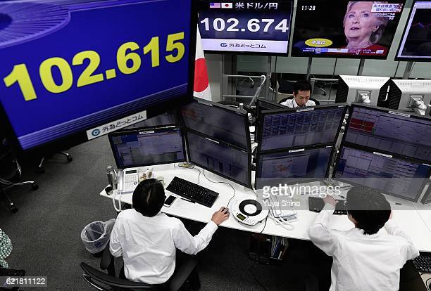Employees of a foreign exchange trading company work near monitors displaying Democratic presidential nominee Hillary Clinton on US presidential...