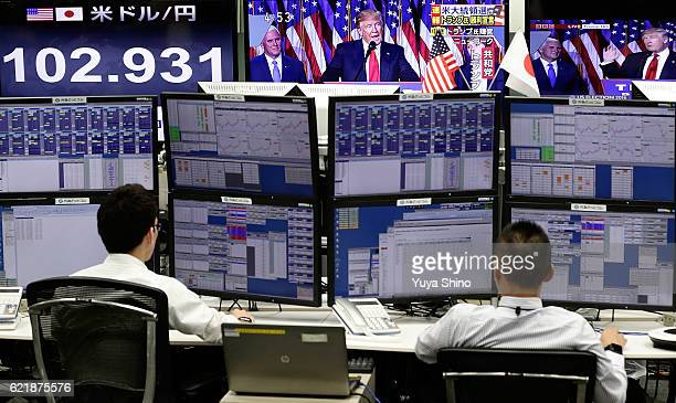 Employees of a foreign exchange trading company work near monitors displaying TV news of Republican Presidentelect Donald Trump as he gives his...