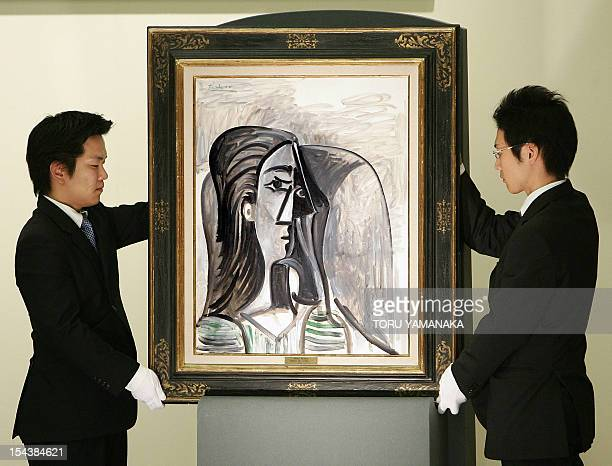 Employees of a Japanese auction house display the oil painting 'Busta de Femme' by Pablo Picasso in his Cubist style in 1960 at an auction in Tokyo...
