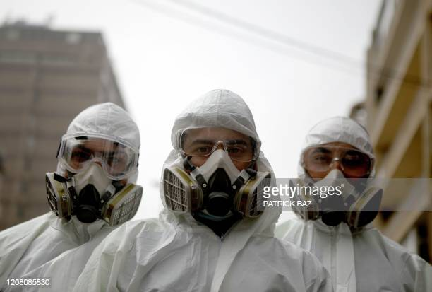 TOPSHOT Employees of a Lebanese public health company pose with their protective gear on in Beirut March 24 as the eastern Mediterrean country called...