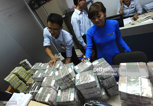 Employees of a local Asia Commercial Bank outlet arrange bricks of dong bank notes sent in from the state bank in Hanoi on August 23, 2012....