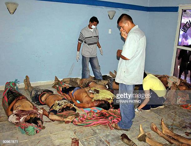 Employees of a morgue look 16 June 2004 in La Gabarra 700 Km northeast of Bogota at the bodies 34 coca workers executed in Tuesday's early morning...