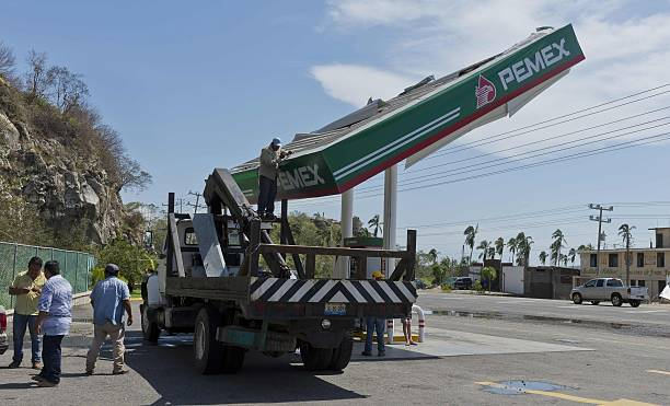 Employees Of A Pemex Petrol Station Work To Fix The Roof Of One Of