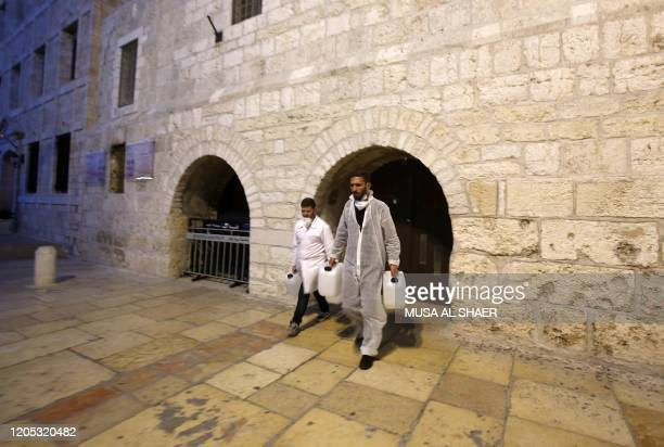 Employees of a private company walk out of the Church of the Nativity in the West Bank city of Bethlehem, after spraying sanitisers as a preventive...