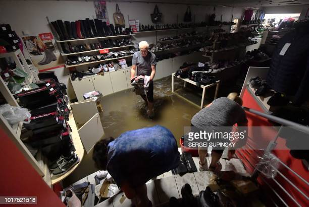 Employees of a shoe shop in the center of Kiev save the footwear and other items from floods following a heavy overnight storm on August 16 2018 Some...