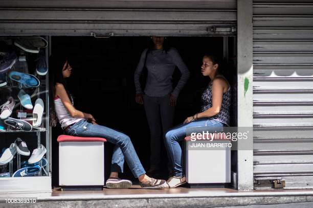 TOPSHOT Employees of a shoe store are pictured during a power cut in Caracas on July 31 2018 A power failure cut electricity to 80 percent of the...