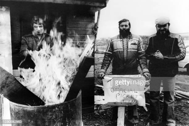 """Employees of a transport compagny keep warm near a fire and hold a banner saying """"TGWU official picket line"""", on January 15, 1979 in Esat London,..."""