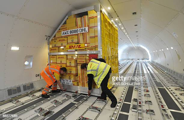 Employees of air cargo company AeroLogic fix boxes in an aircraft at Leipzig/Halle airport near the eastern German town of Schkeuditz on June 19 2009...