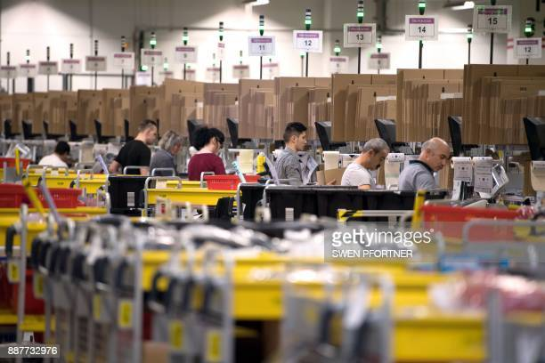 Employees of American electronic commerce company Amazon prepare products for dispatch in Bad Hersfeld central Germany on December 7 2017 To cope...