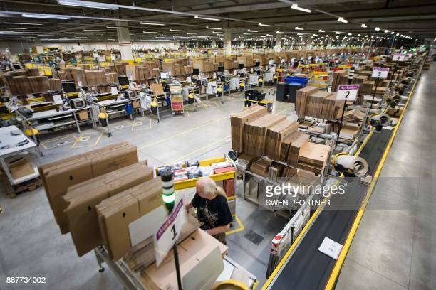 Employees of American electronic commerce company Amazon prepare items for dispatch in Bad Hersfeld central Germany on December 7 2017 To cope with...