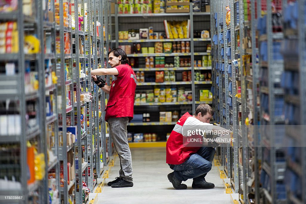 Employees of an Auchan Drive prepare goods ordered by the ...