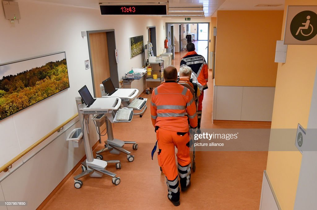 Employees Of An Emergency Service Push A Stretcher Carrying Person Across The Hallway