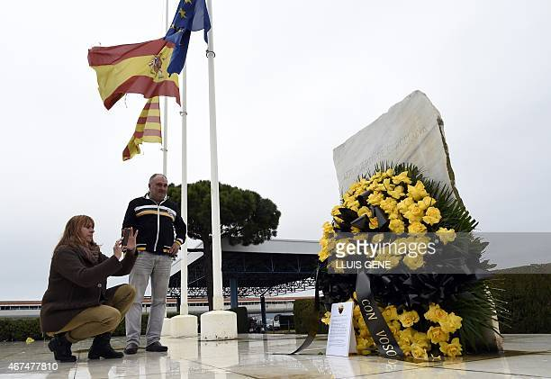 Employees of Barcelona's El Prat airport take pictures of a wreath of flowers displayed in honour of the victims of the crash of an Airbus A320, in...