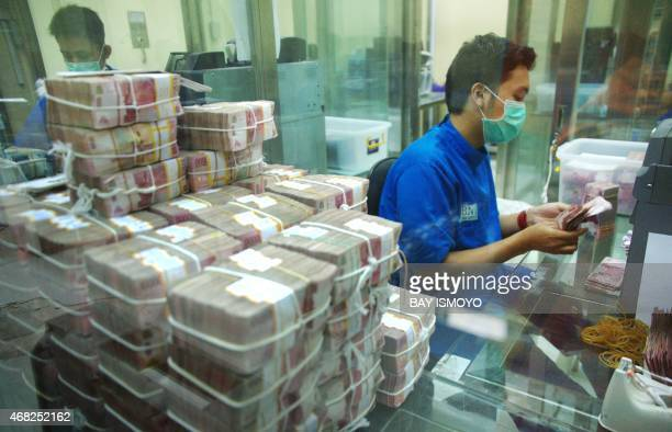 Employees of BNI bank an Indonesian stateowned bank prepare rupiah banknotes for their ATMs and branch offices in Jakarta on April 1 2015 Indonesia's...