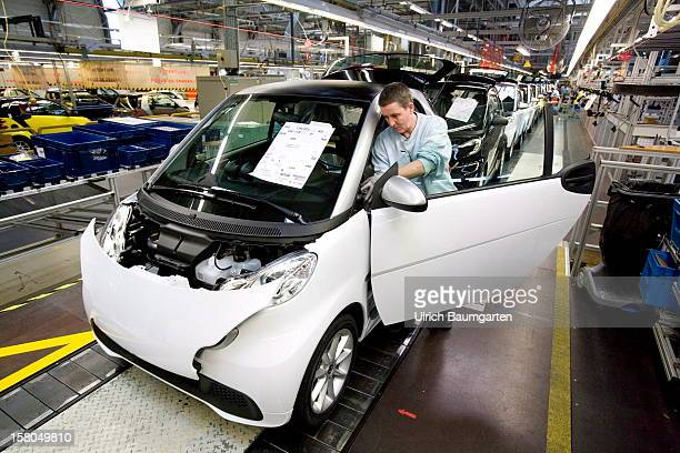Employees of car maker Daimler AG assemble a Smart Fortwo Electric Drive car at the company's Smartville plant on December 6 2012 in Hambach France...