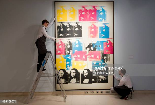 Employees of Christie's auction house pose by US artist Andy Warhol's Colored Mona Lisa painted in 1963 which is estimated to sell for approximately...