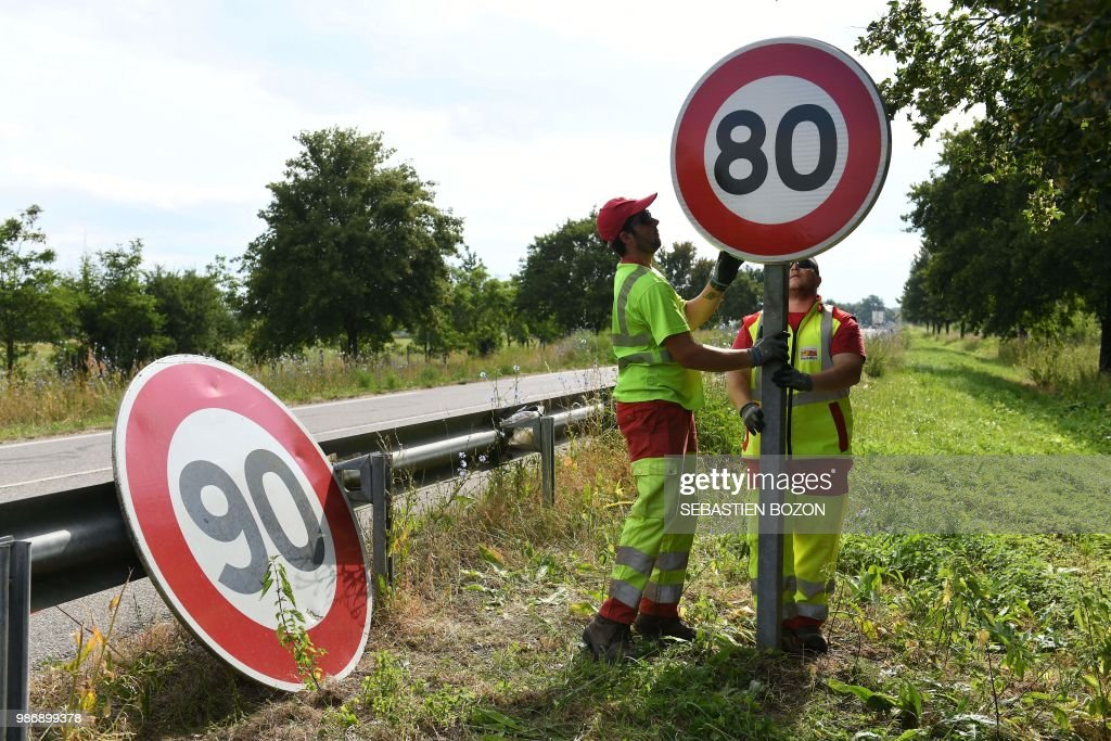 Employees of DIR Est replace a 90 Km/h speed limit sign with