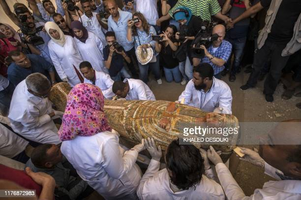 Employees of Egypt's ministry of antiquities open a sarchphagus displayed in front of Hatshepsut Temple in Egypt's valley of the Kings in Luxor on...