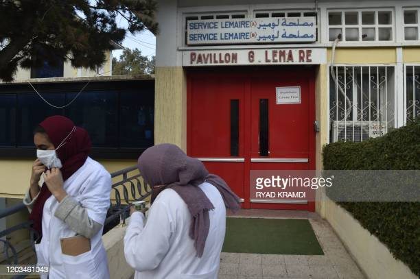 Employees of El-Kettar hospital wear protective masks as they stand at the entrance of one of its units, in the Algerian capital Algiers on February...