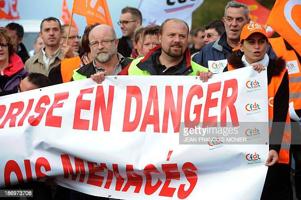 """Employees of """"FagorBrandt"""", subsidiary of the Spanish electrical appliance maker """"Fagor"""", hold a banner as they demonstrate on November 5, 2013 in..."""
