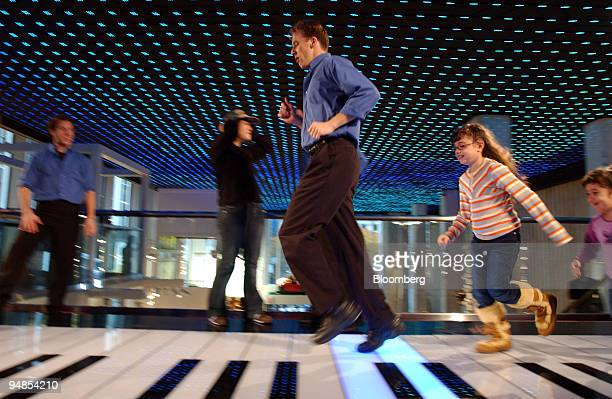 Employees of FAO Schwarz and visitors play the piano seen in the Tom Hanks movie Big as the store's doors reopen for the holiday season after being...