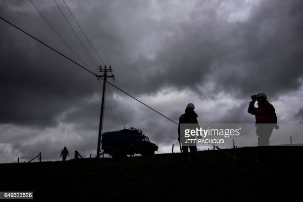 Employees of French national electricity grid company Enedis work to repair high voltage lines on March 7 near Amplepuis, central France, after the...