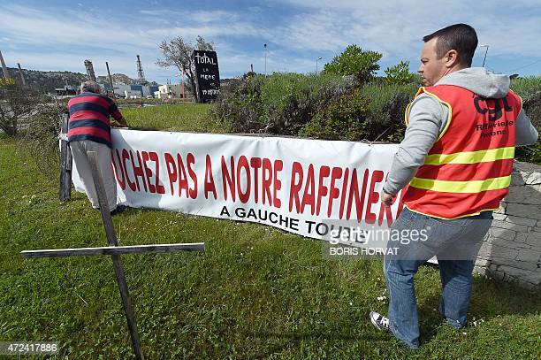 Employees of French oil giant Total's La Mede refinery hang a banner on May 7 2015 in ChateauneuflesMartigues southern France as members of the CGT...