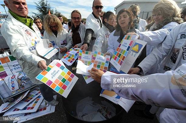 Employees of French pharmaceutical group Sanofi arrive to burn copies of the group's code of ethics during a demonstration on November 8 2012 in...
