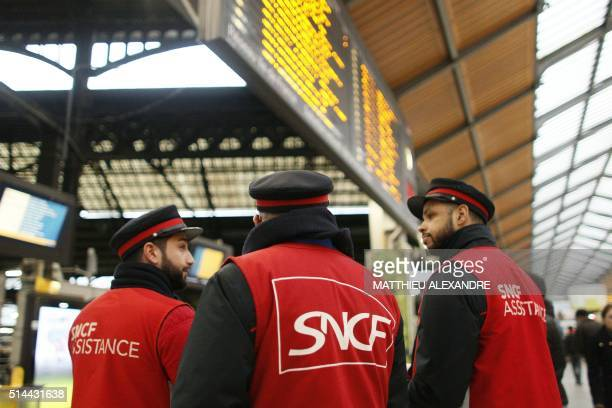 Employees of French railway operator SNCF gather as they guide commuters at the Saint Lazare railway station early on March 9 2016 in Paris France...