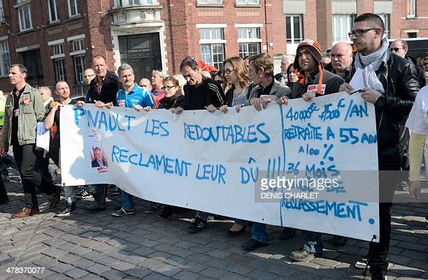 Employees of French retail company 'La Redoute' hold a banner as they take part in a protest against layoffs and calling for compensation for...