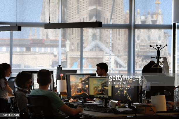 Employees of French video game developer Gameloft work on their computers during a visit to the company's studios of Barcelona with the Sagrada...