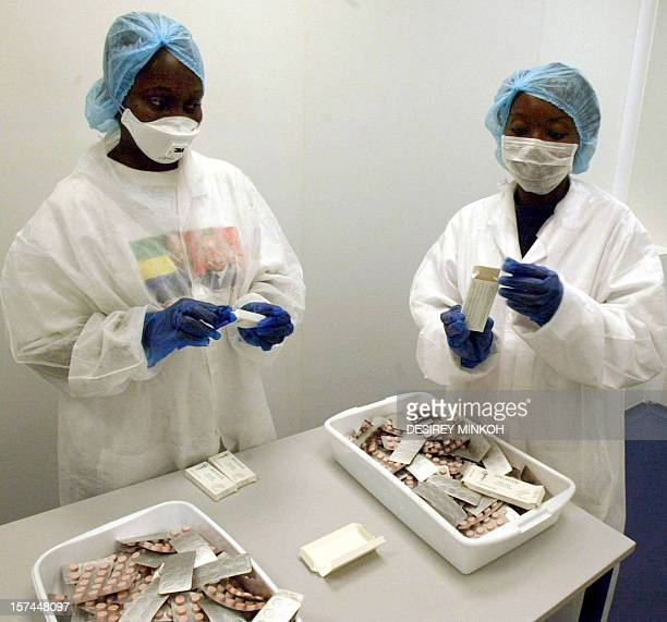Employees of Gabonese pharmaceutical factory Sogafam fill boxes of pills 04 March 2005 at the plant in Owendo south of Libreville Sogafam is the...