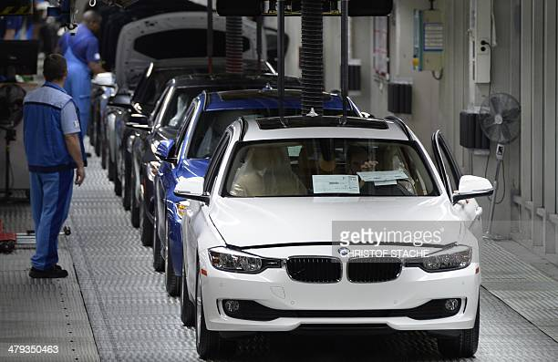 Employees of German car maker BMW work on an assembly line for BMW cars at the company's plant in Munich southern Germany on March 18 2014 German...
