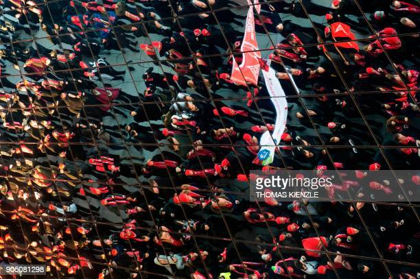 Employees of German car maker Porsche are reflected in the glass roof of the Porsche museum during a demonstration as part of a warning strike on...