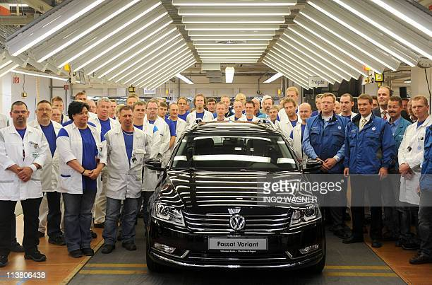 Employees of German car manufacturer Volkswagen pose for a photo beside a VW Passat Kombi the 10 millionth car produced at the company's plant in the...