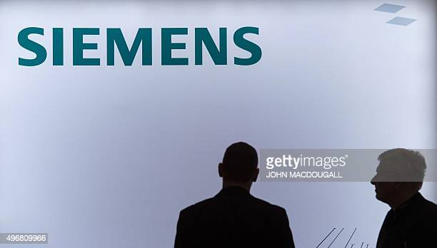 Employees of German industrial giant Siemens stand in front of a company logo during a press conference in Berlin on November 12 upon the...