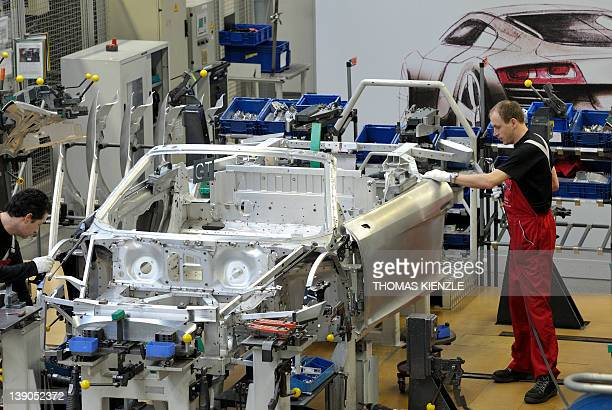 Employees of German luxury car maker Audi work on an Audi R8 sportscar at an assembly line of the Audi plant in Neckarsulm southwestern Germany on...