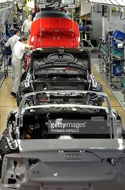 Employees of German luxury car maker Audi work on Audi A5 and A4 cars on the assembly line at the Audi plant in Neckarsulm southwestern Germany on...