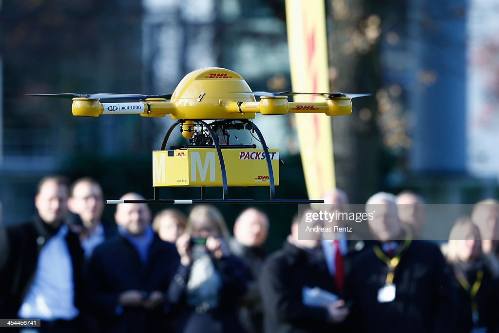 Employees Of German Postal Carrier Deutsche Post And Visitors Watch As A Quadcopter Drone Arrives With