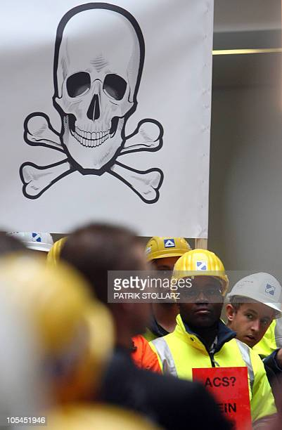 Employees of Germany's largest construction company Hochtief wearing a helmets stand next to a banner with a skull and crossbones inside of their...