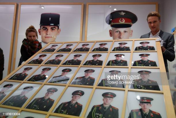 Employees of Grisebach auction house hang giant photos by photographer Frank Thiel of the Allied soldiers who once patrolled Berlin that have been...