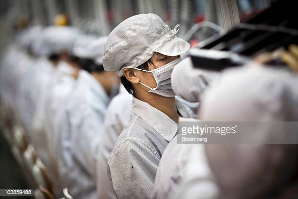 Employees of Hon Hai Precision Industry Co Ltd work along a production line in the Longhua Science and Technology Park also known as Foxconn City in...