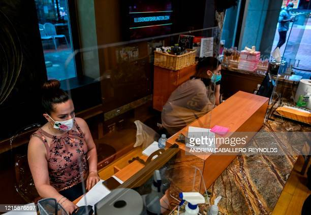 Employees of Illusions of Shirlington hair salon take appointments from clients as they sit behind plexiglass barriers a day before they reopen in...