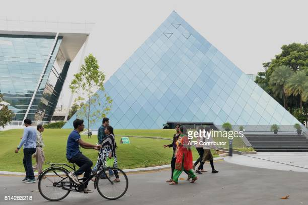 Employees of Indian Software giant Infosys Technologies Limited walk in the campus of the company's headquarters in Bangalore on July 14 2017 / AFP...