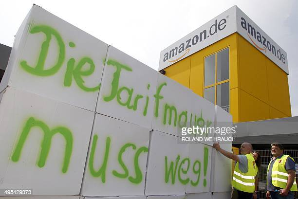 Employees of internet retail giant Amazon built up a wall with an inscription reading 'Hence with the tariff wall' as they stage a strike in front of...