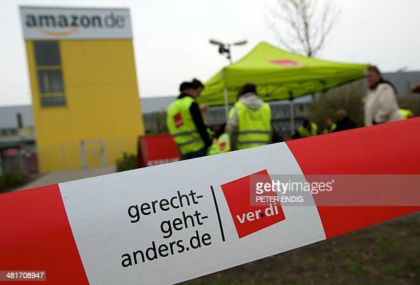 Employees of internet retail giant Amazon stand in front of their company's logistics centre in Leipzig eastern Germany as they stage a strike on...
