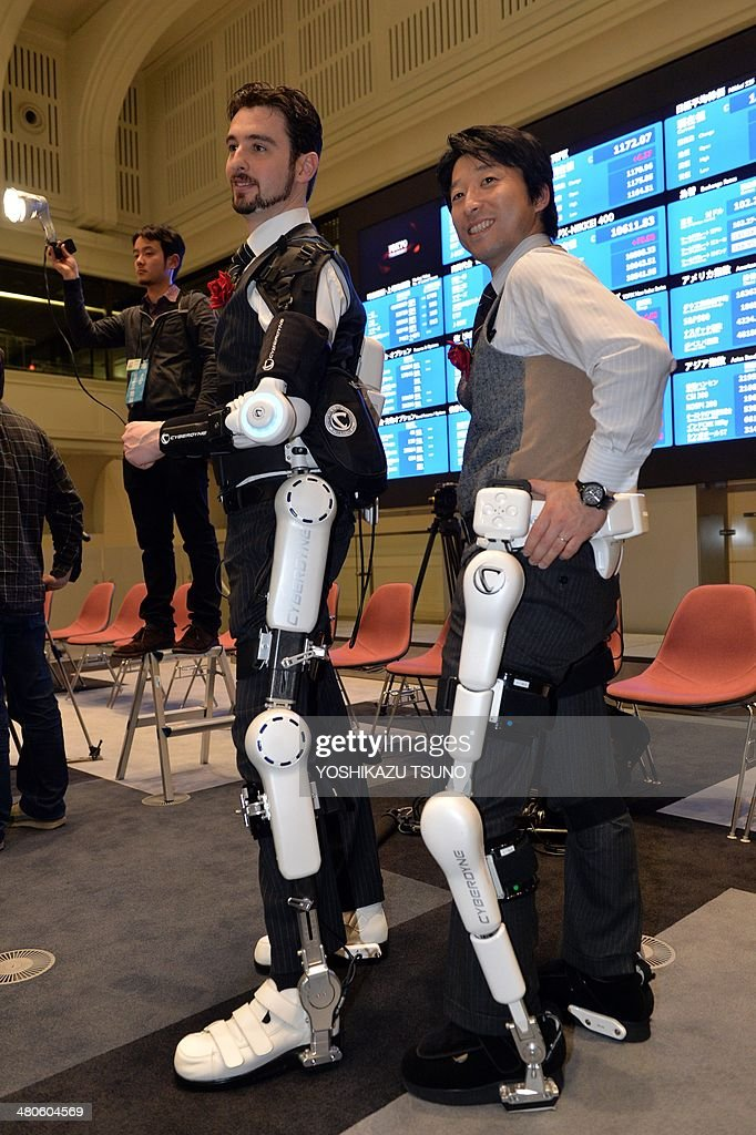 Employees of Japanese robot venture Cyberdyne, display the robot suits Hybrid Assistive Limb (HAL), which is designed to learn the user's motion and assist their movement, can be used for the rehabilitation of disabled and assist elderly people, as the company was listed at the Tokyo Stock Exchange's (TSE) Mothers market, aimed at providing venture companies access to funds at an early stage of their development at the TSE on March 26, 2014. Cyberdyne, the maker of a battery-powered exoskeleton robot suit, made its stock market debut, as the firm looks to raise money to boost its research. AFP PHOTO / Yoshikazu TSUNO