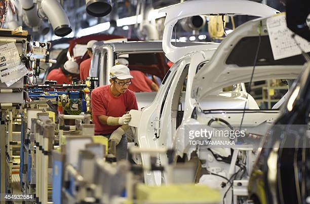 Employees of Japan's auto giant Nissan Motor work at an assembly line of its Oppama Plant in Yokosuka suburban Tokyo on September 8 2014 The plant...