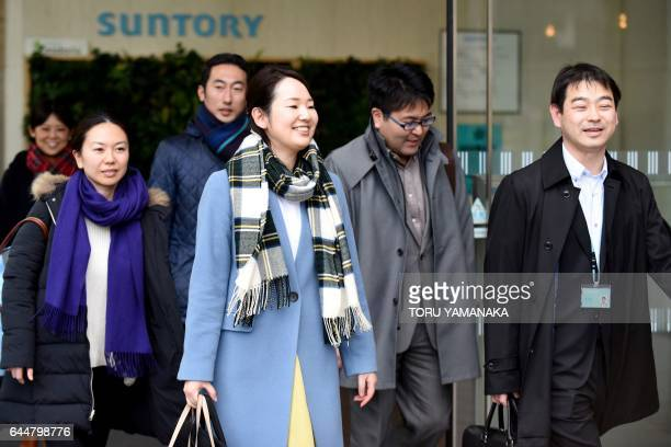 Employees of Japan's brewing and distilling company group Suntory leave their office after finishing work at three o'clock in Tokyo on February 24...
