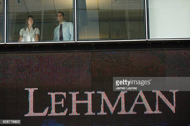 Employees of Lehman Brothers look out at a crowd of media outside the company's headquarters in Midtown Manhattan on the day that Lehman filed for...